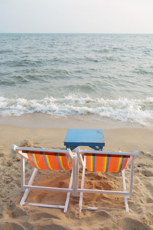 Two chair with a table on the beach