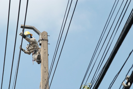 Electrician maintenance and install the power cord on the high pole Stock Photo
