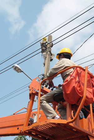 Electricians maintenance and install the power cord on the high pole
