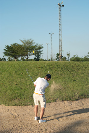 Asian amature golfer hitting a golf ball on bunker