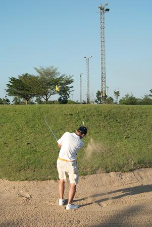 Asian amature golfer hitting a golf ball on bunker