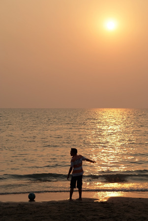 A boy playing football on the beach with sunset