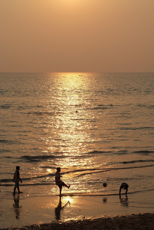 Three boys  playing football on the beach with sunset