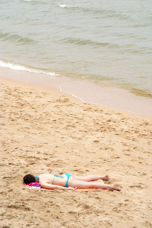 A traveler lie down on the beach for sunbath