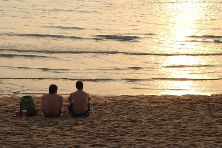 Two mens are relaxing on the beach with sunset