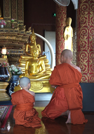 Two monk are praying in front of the statue buddha