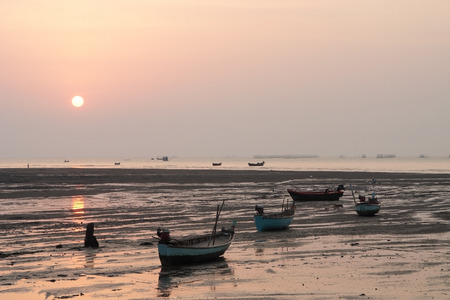 Fishing boats was stationary on the beach with sunset