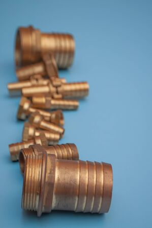 Vertical photo of brass adapters for connecting a hose and a bolted joints. Photo with shallow depth of field, on a blue background.