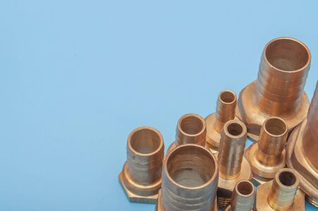 Brass adapters of different diameters, to connect the hose and thread. Water supply equipment. A close-up photo of a blue background with a copy spase.
