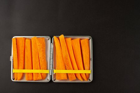 Cigarette case with carrot slices Concept of quitting smoking, healthy lifestyle
