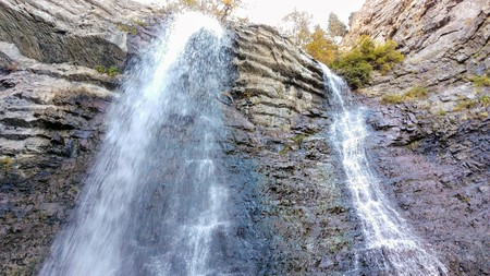 Battle Creek Falls cascading down the layers of rock and spraying the rocks below. Stock Photo