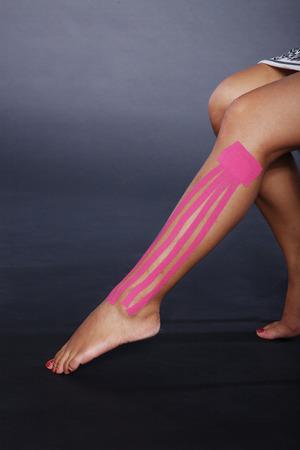 junge hübsche Frau mit Sport Taping am Bein