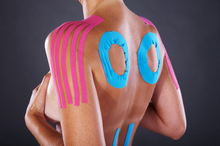 leg calf injury: young pretty woman with sports taping on back and shoulder Stock Photo