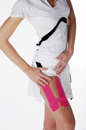 junge hübsche Frau mit Sport-Taping am Bein