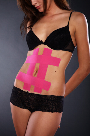 young pretty woman with sports taping on belly photo