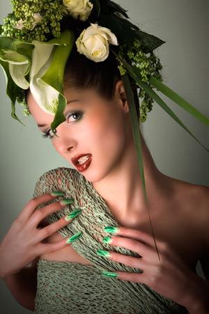 Mode-Modell im grünen Design und Blumen