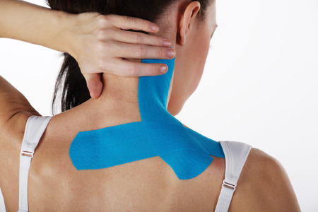 young pretty woman with sports taping on neck and shoulder photo