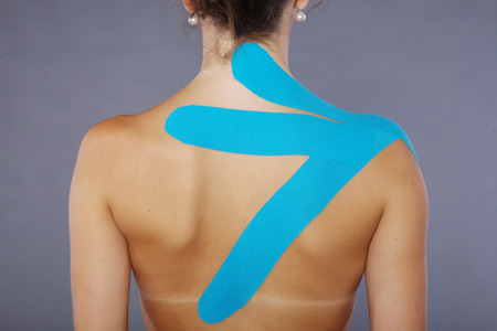 leg calf injury: young pretty woman with sports taping on neck and shoulder
