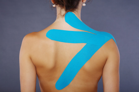 young pretty woman with sports taping on neck and shoulder