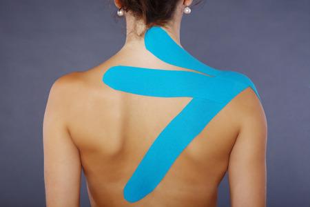 Junge hübsche Frau mit Sport-Taping an Hals und Schulter Standard-Bild - 28589838