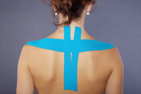 taping: young pretty woman with sports taping on neck and shoulder
