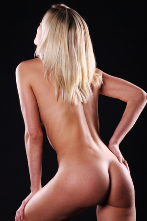 Beautiful naked female body on a dark background Stock Photo