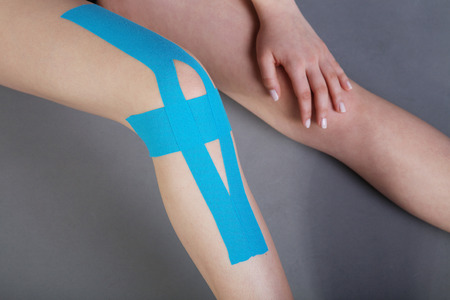 leg calf injury: young pretty woman with sports taping on knee