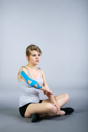 young pretty woman with sports taping on arm photo