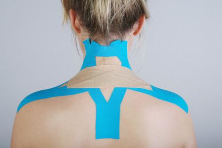 junge hübsche Frau mit Sport-Taping an Hals und Schulter