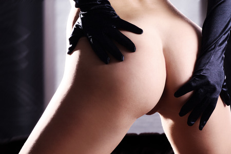 Nude butt of a woman with gloves Stock Photo