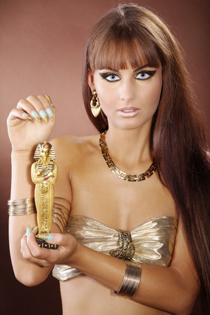 fashion model in cleopatra style and Egyptian figurines photo