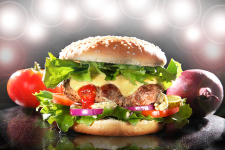 hamburger topped with onion and tomato photo