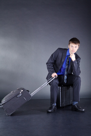 Businessman with suitcase while waiting photo