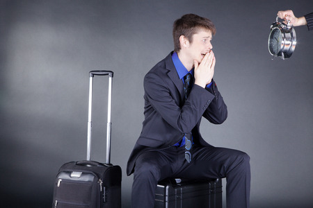 Businessman with suitcase and clock photo