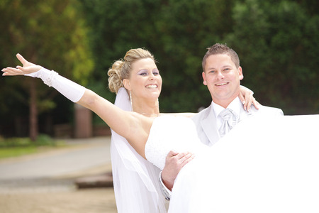 beautiful white bride is worn by the groom photo
