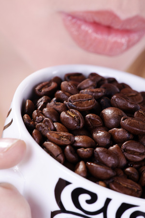 beautiful woman drinking from coffee cup beans photo