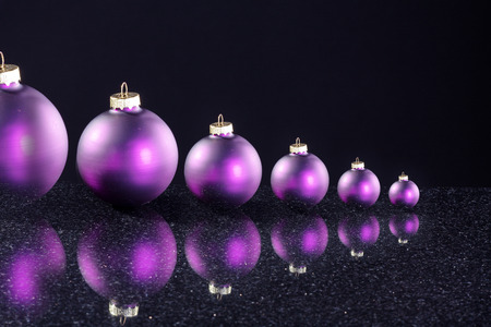 several Purple christmas balls in succession photo