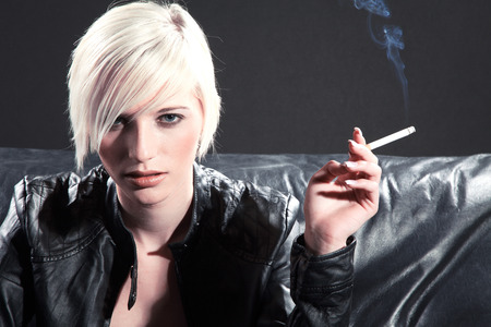 smoking girl: pretty woman with cigarette on couch Stock Photo