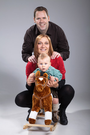 parents with small sweet boy on rocking horse photo