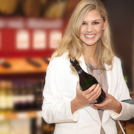 pretty young woman in supermarket with champagne photo