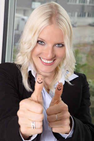 thumps up: Business woman in office thumps up Stock Photo