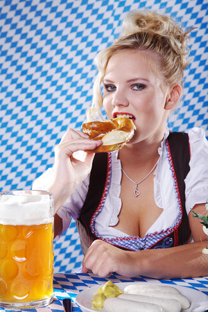 young pretty woman in Bavarian style and eating photo