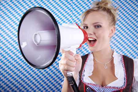 beautiful woman in Bavarian outfit and megaphone photo