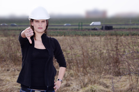thump: woman with construction helmet in nature with thump down