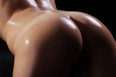 Nude butt of a woman with oil