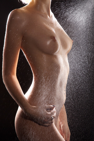 Nude wet female body and water
