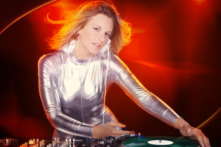 dj woman on the mixing console with headphones photo