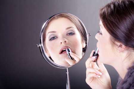 beautiful woman with applying makeup with mirror photo