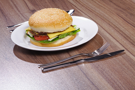 sesame seed: hamburger verviert at the table with cutlery Stock Photo
