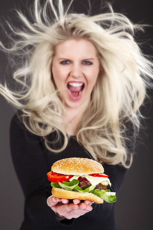 beautiful model with flying hair presents a Burger with cheese photo